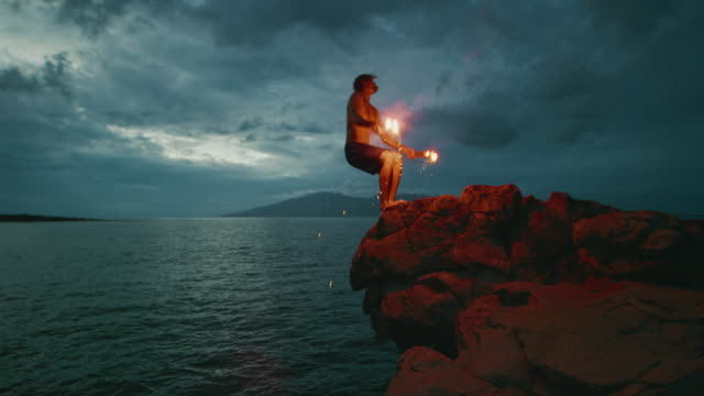 Extreme stuntman does a backflip with fire into the sea Extreme cliff jumping man backflipping off of an sea cliff with burning red hot flares, epic stuntman moments, people are awesome cliff jumping stock videos & royalty-free footage