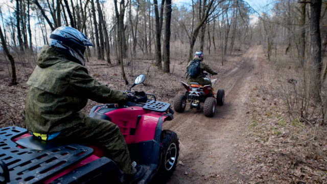 extreme vacation in the woods on the atv. men engage in motor sport, quad bike is an ideal means for riding on country roads. all wheel drive helps to overcome obstacles, and to conquer the terrain - bike tire tracks video stock e b–roll