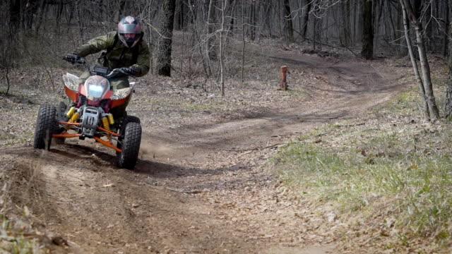 vacanza estrema nei boschi sull'atv. gli uomini praticano sport motoriso, il quad è un mezzo ideale per guidare su strade di campagna. tutta la trazione integrale aiuta a superare gli ostacoli e a conquistare il terreno - supercross video stock e b–roll