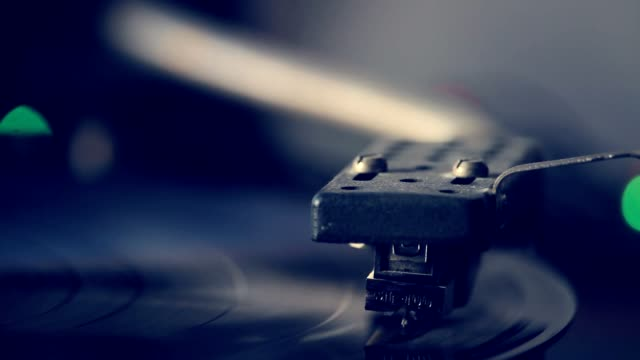 Extremely close-up of antiquarian record player with the needle playing record album on a vintage turntable, vinyl record spinning, selective focus