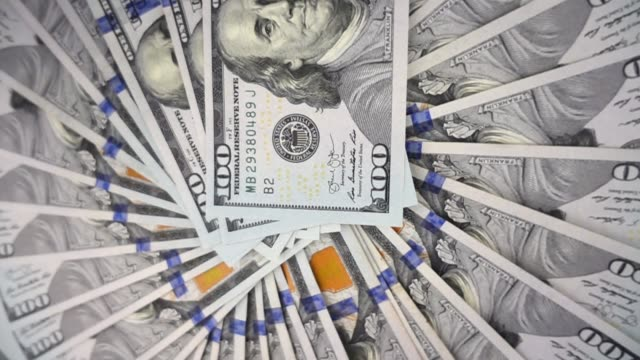 VIDEO, extremely close-up of US dollars banknotes, rotational motion