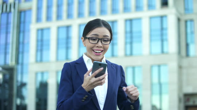 extremely happy woman in suit reading good news, office worker getting promotion - promemoria video stock e b–roll