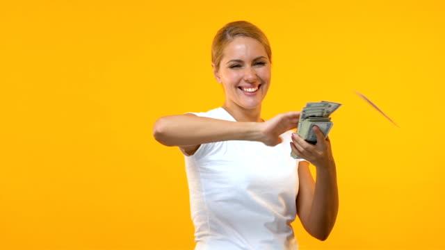 vidéos et rushes de femme extrêmement heureuse jetant des dollars contre le fond orange, gagnant de loterie - lancer