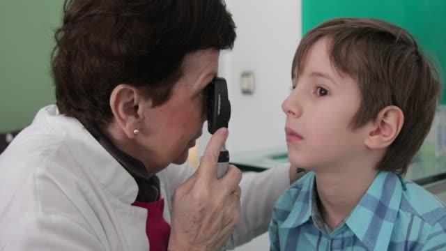 Eye doctor examing little boy eye video