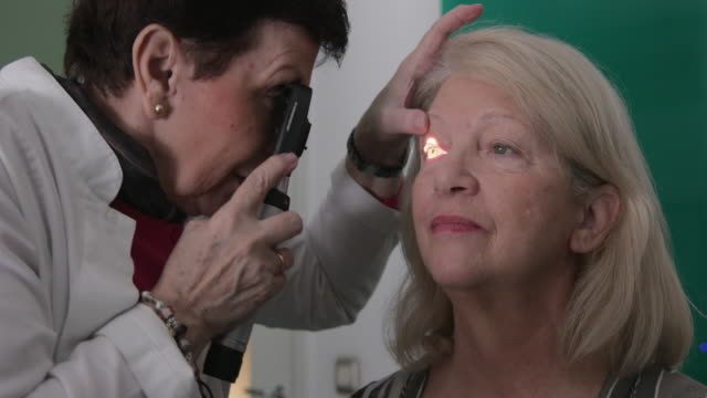 Eye doctor looking into patient eye Eye doctor looking into patient eye with ophthalmoscope eye exam stock videos & royalty-free footage