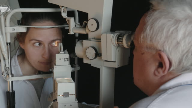 Eye exam with a slit lamp. Young woman examining eyes at ophthalmologist. White collar workers. Active seniors at their work place. Closeup of mid 30's brown eyed woman having her eyes examined at optometrists office. Her head is placed into tomography machine and light beam is shining through her retina and lens. An experienced ophthalmologist is doing her eye exam with a slit lamp. eye exam stock videos & royalty-free footage