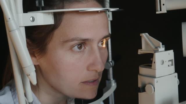 vidéos et rushes de cu, examen de l'œil avec une lampe à fente. jeune femme examinant des yeux à l'ophtalmologiste. les cols blancs. personnes âgées actives sur leur lieu de travail. - rétine