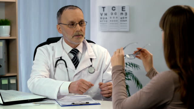 Eye examination, ophthalmologist choosing eyeglasses for patient, checkup video