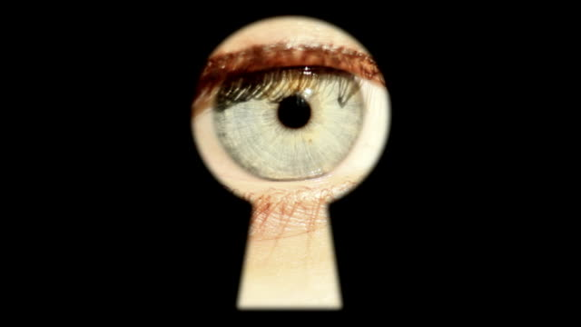 Eye is peeking through the keyhole HD A gray eyed girl is peeking through the locked door keyhole stock videos & royalty-free footage