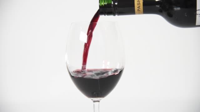 auge auf rotwein gießen gegen weiß - weinglas stock-videos und b-roll-filmmaterial
