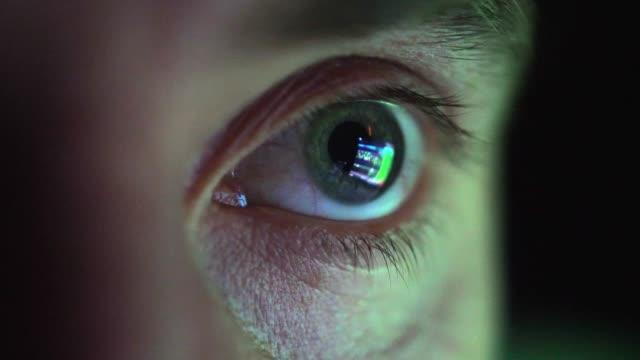 vidéos et rushes de oeil regardant l'écran d'ordinateur programmant le code de hacker réfléchissant dans le globe oculaire - violation d'accès informatique