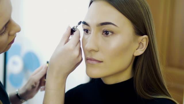 stockvideo's en b-roll-footage met oog make-up vrouw oogschaduw poeder toe te passen. mooie vrouw gezicht. perfecte make-up. beauty beli parfum mode. wimpers. cosmetische oogschaduw. close-up. slow motion - ooglid