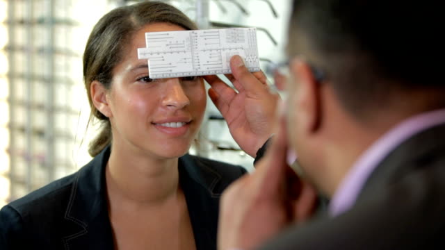 Eye measuring for spectacles A dispensing optician measures the eyes of a client for a glasses fitting in a retail optician store. instrument of measurement stock videos & royalty-free footage