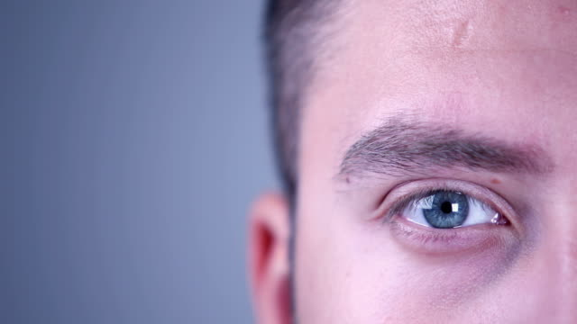 eye of a young man looking at camera - battere le palpebre video stock e b–roll