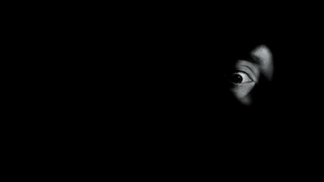 глаз испуганного свидетеля преступления, смотря через замочную скважину, лечение жизни, крупным планом - замочная скважина стоковые видео и кадры b-roll
