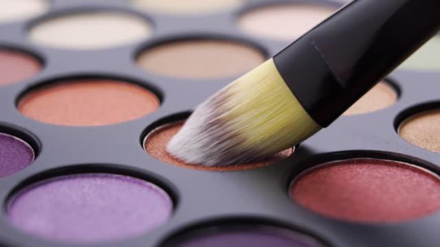 vídeos de stock e filmes b-roll de eye shadow palette and brush close up shot - sombra para os olhos
