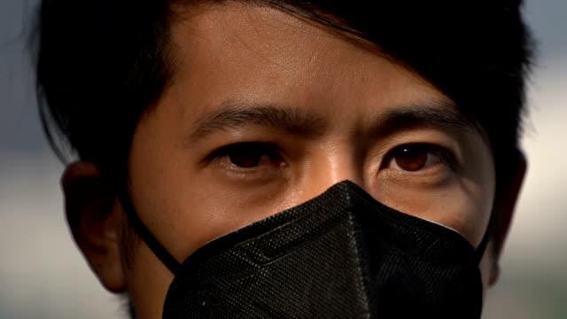 cu slomo-kirlilik maskesi ile asya man göz çekimi - maske stok videoları ve detay görüntü çekimi