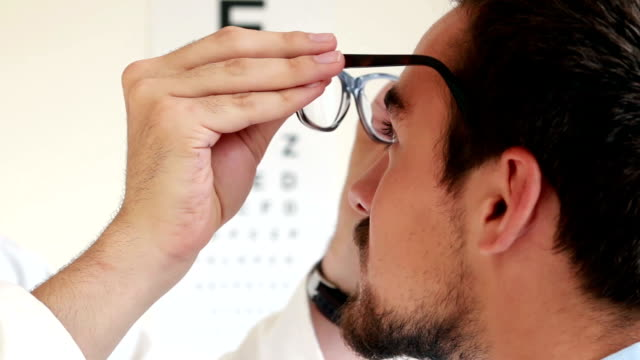 Eye test chart, Optician. Optician putting glasses on a young man, over shoulder the man turns to the eye test chart the focus moves to the letters on the wall. Selective focus. eye exam stock videos & royalty-free footage