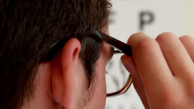 Eye test. Young man putting on glasses to use eye test chart. Selective focus. eye exam stock videos & royalty-free footage