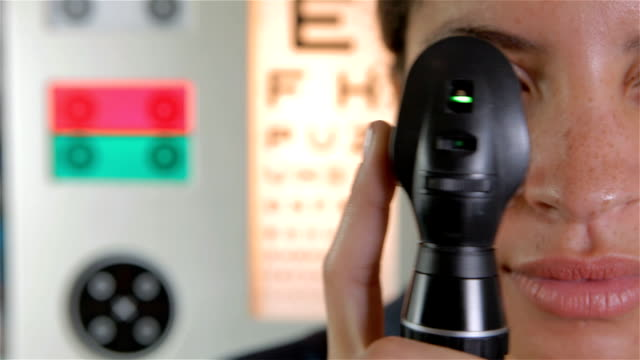 Eye test with magnifying tool A representation of an eye test with a magnifying tool in the foreground, looking in to camera and an eye test chart in the background. eye exam stock videos & royalty-free footage