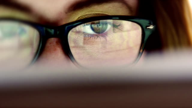 Eye watching display Stock video close up dolly clip of an observant young woman eye as she peruses a large computer display, the reflection of the windows & media contents are seen in her glasses a she opens & closes data. Researching websites general information she scrutinizes the screen. adult stock videos & royalty-free footage