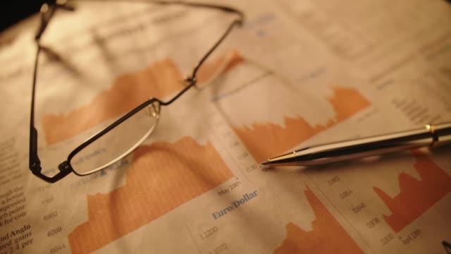 vidéos et rushes de lunettes de vue et un stylo sur journal inscription bourse - book
