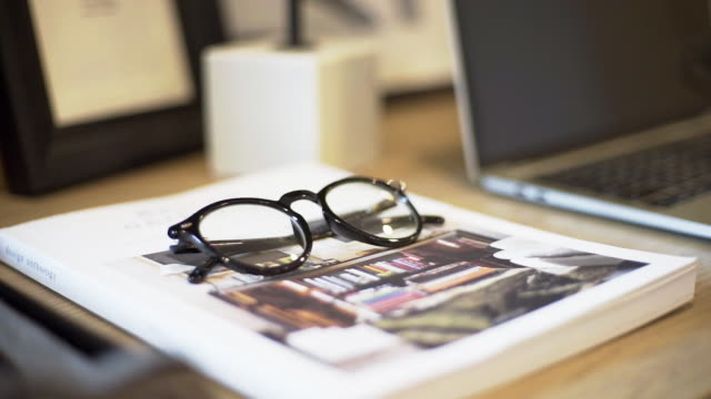 Eyeglasses on the magazine with laptop on a wooden table indoors.