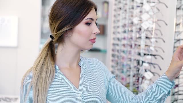 眼鏡店。視力補正用眼鏡を選び女性 ビデオ