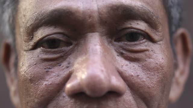 eyes and face of worried asian man looking at camera - male eyes bildbanksvideor och videomaterial från bakom kulisserna