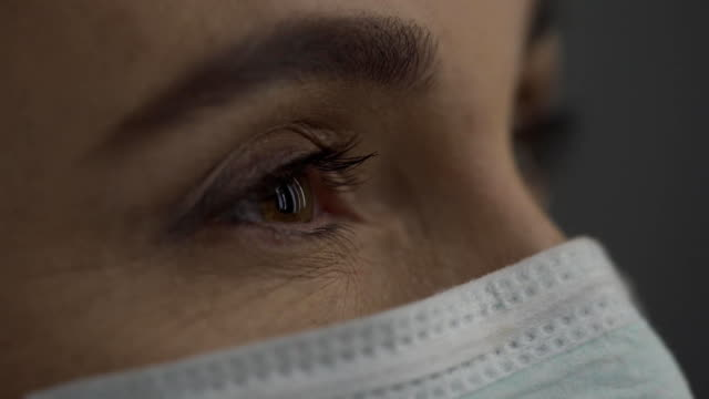 eyes of a middle-aged woman's doctor. view from the side - mask surgery video stock e b–roll