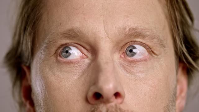 stockvideo's en b-roll-footage met ogen van een bang blanke man rondkijken - ongerustheid