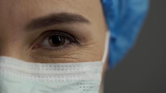 微笑的護士或醫生的眼睛在外科口罩 - surgeon 個影片檔及 b 捲影像