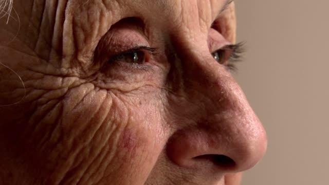 eyes of elderly woman with wrinkles smiling - морщинистый стоковые видео и кадры b-roll