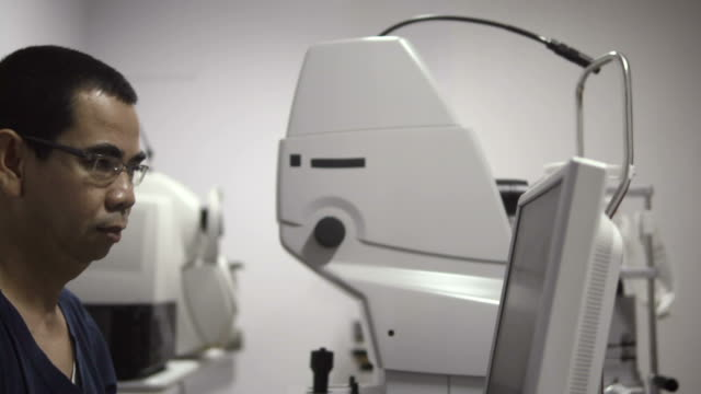 Eyesight exam in clinic with Asian doctor and female patient video