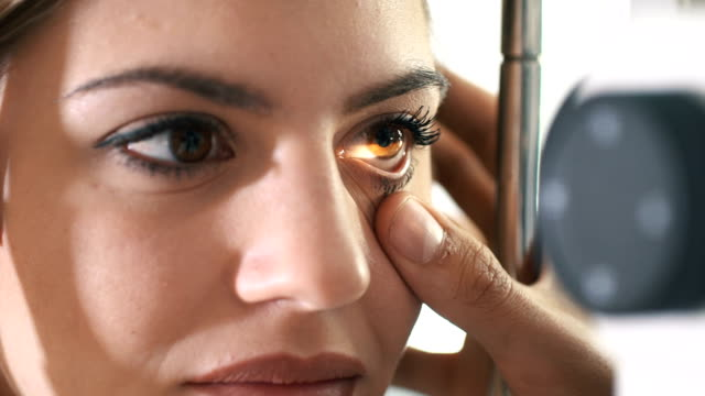 Eyesight exam. Closeup of mid 20's brown eyed woman having her eyes examined at optometrists office. Her head is placed into tomography machine and light beam is shining through her retina and lens. HD eye exam stock videos & royalty-free footage