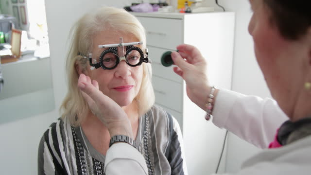 Eyesight testing Female doctor testing eyesight of senior patient with eye trail frame ophthalmologist stock videos & royalty-free footage
