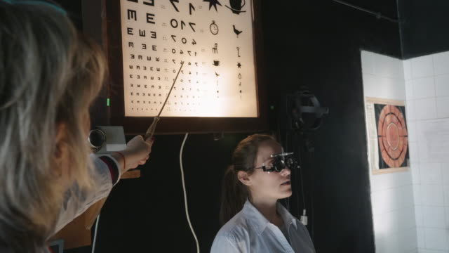 Eyesight testing with a phoropter and an eye chart. Young woman examining eyes at ophthalmologist. White collar workers. Active seniors at their work place. Female Doctor. Closeup of mid 30's brown eyed woman having her eyes examined at optometrists office. Female doctor testing eyesight of the patient with eye trail frame and eye chart. eye chart stock videos & royalty-free footage
