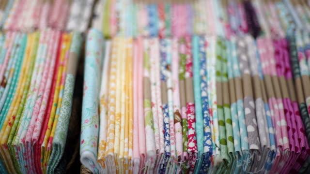 vídeos de stock e filmes b-roll de fabric pile of colorful textiles with flowery printed sheets, handmade and handicraft concept. - edredão