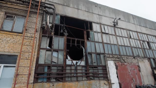 facade of old industrial building for demolition in cloudy day, broken glass and destroyed frames - foreclosure stock videos & royalty-free footage