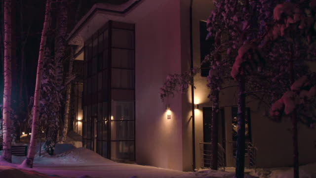 Facade of the big house in the late winter evening illuminated by colorful flashing light of an emergency car. Stock footage. Outdoors view of the cottage in snowy winter at night