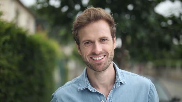 genç mutlu rahat bir adam gülümseyen yüz - sarı saç stok videoları ve detay görüntü çekimi