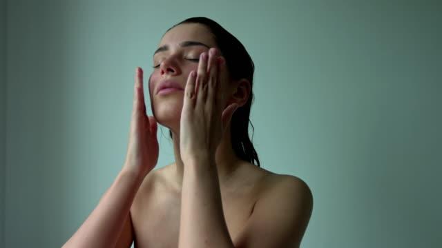 vidéos et rushes de massage du visage et du cou. jeune femme nue massant la peau de visage et de cou. thérapie rajeunissante. - peau humaine