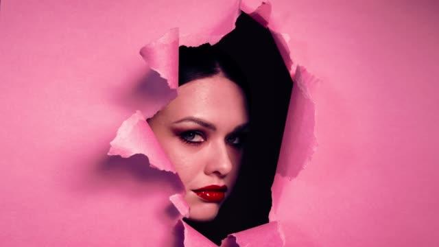 schönes mädchen mit hellen make-up in zerrissenen öffnung in rosa papierhintergrund zu stellen. - lippenstift stock-videos und b-roll-filmmaterial