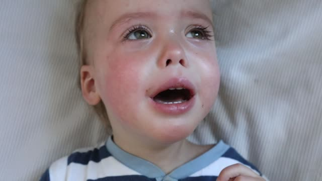 Face crying baby boy in crib at home video