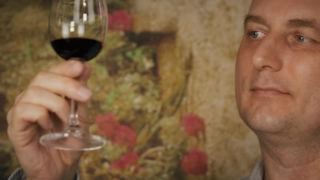 Face man looking on red wine in glass before tasting. Man drinking red wine video
