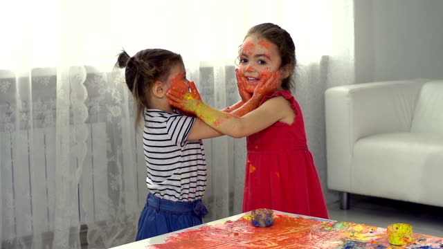 Face Mask Two little girl friends smearing paint on each other's face playroom stock videos & royalty-free footage