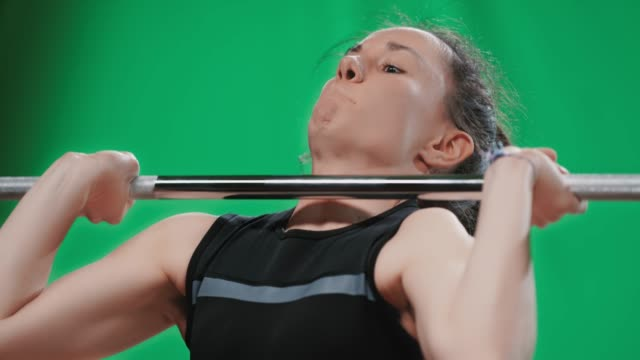 slo mo face of a female weightlifter as she raises the barbell above her head - potere femminile video stock e b–roll