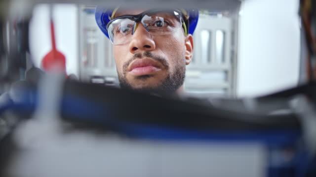 ds faccia di un elettricista maschio guardando nel pannello elettrico e fili di collegamento - occhiali protettivi video stock e b–roll