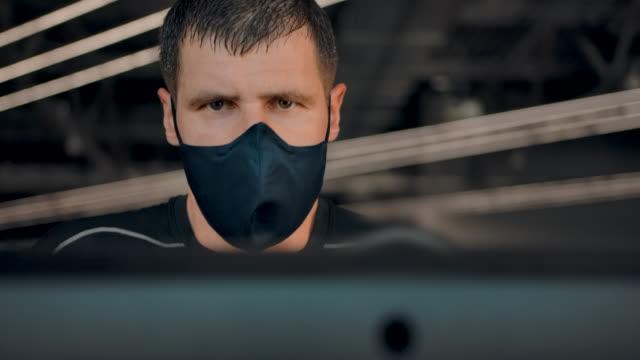 vídeos de stock e filmes b-roll de face of a moderate strong man on treadmill wearing protective mask from viruses - aparelho de musculação