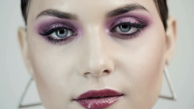Face of a young beautiful girl with pink eyeshadows and pink lip gloss. Close up face of a young beautiful girl with pink eyeshadows and pink lip gloss. Pink makeup. Open your eyes. Silver earrings, jewelry. Beauty saloon. eyeshadow stock videos & royalty-free footage